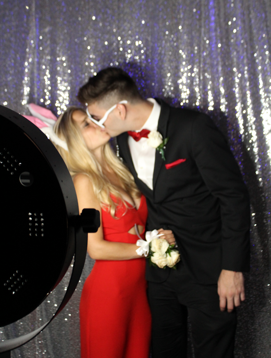 Couple shares a kiss for a boomerang Video on our social media photo booth at an event in Miami Beach, FL